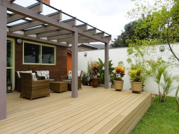 Pergola e deck feitos de madeira plástica na área esterna, cobertos com vidro fosco