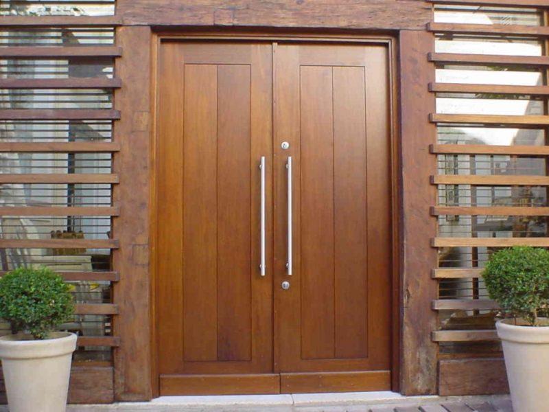 Porta de madeira de luxo, modelo com duas folhas, e puxador em metal.
