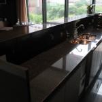 Já essa bancada, é feita em granito preto, bastante elegante para o design de cozinhas modernas e práticas.