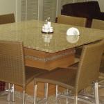 Um modelo bem simples de mesa com tampo de granito marrom, combinando com as cadeiras