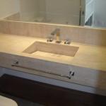Pia feita em granito claro para o banheiro.