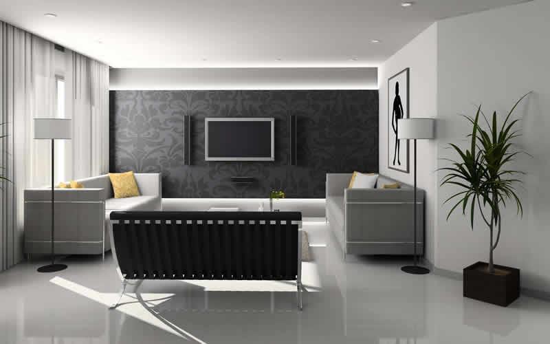 Sala de estar sofisticada decora com tons de cinza e preto, contado com itens como abajur, quadros, sofá igualmente sofisticados