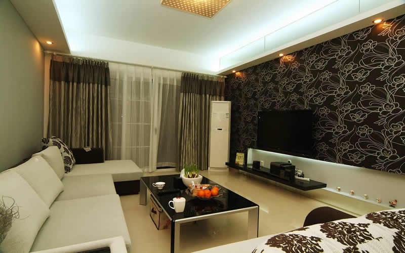 Sala de estar decorada com tons claros e escuros, com papel de parede.