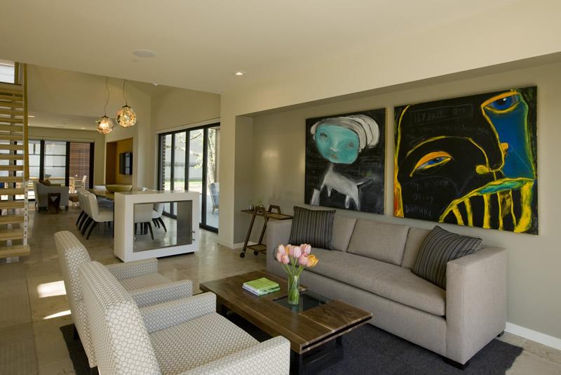 Decoração de sala de estar ampla com quadros, sofás claros e tapete em tom escuro