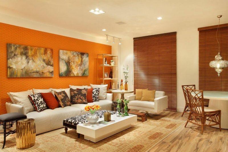 Decoração de parede de sala de estar com mudança de cor para o laranja para quebrar a monotonia