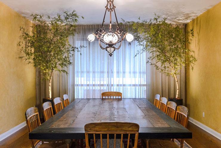 Sala de estar rústica decorada com dois vasos de bambu mosso artificial