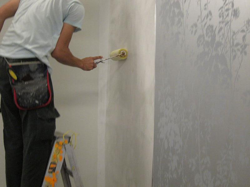 Passando a cola na parede após esta estar limpa e nivelada para a instalação de papel de parede