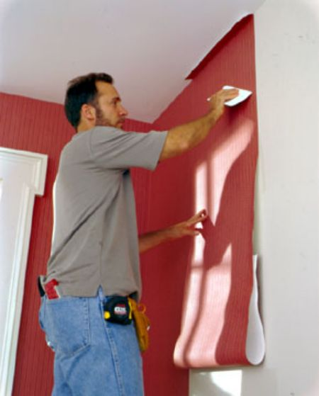 Passando uma régua para deixar o papel de parede instalado com caimento perfeito