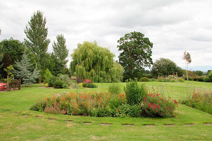 Jardim de residência inglesa em que os canteiros e arvoredos são plantados de forma que pareçam o mais natural possível.