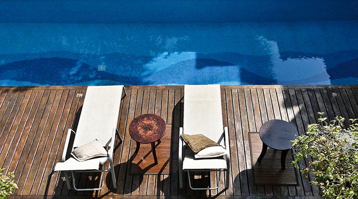 Piscina de Pastilhas de vidro, acompanhada de deck de madeira na borda da piscina