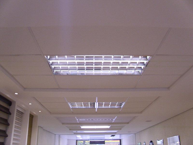 Instalação de luminárias de módulos semelhantes aos das placas de forro mineral.