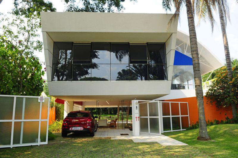 Casa com fachada moderna suspensa sobre pilotís