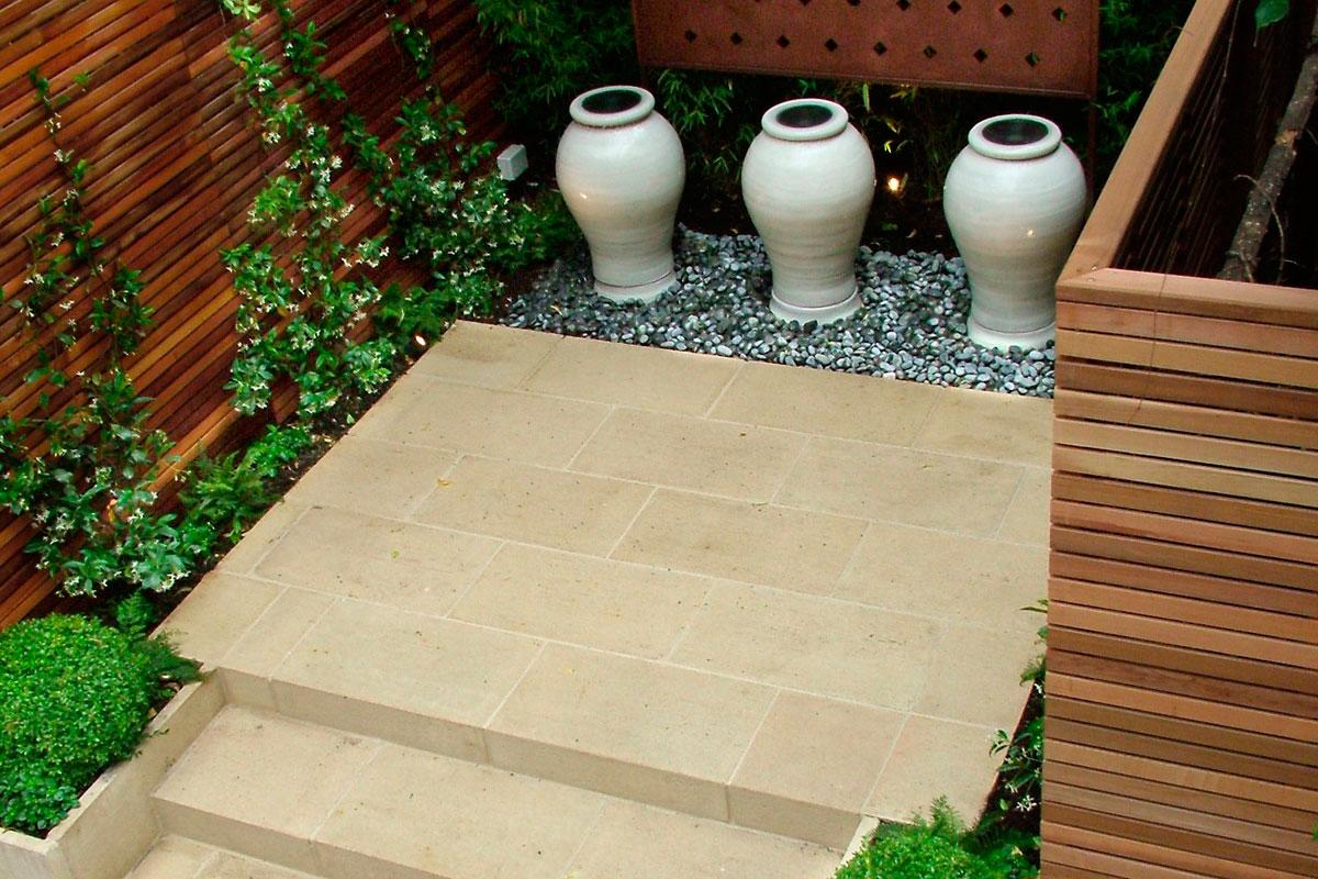 Outra ideia para decorar jardins pequenos é a criação de nichos que também tenham um elemento que funcione como ponto focal, como esses vasos cerâmicos