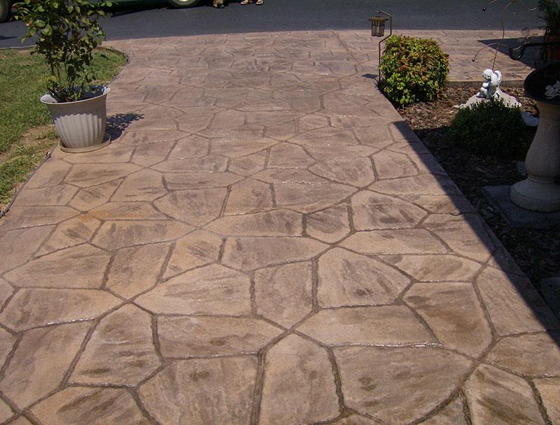 Piso de concreto estampado simulando revestimento de pedras na calçada