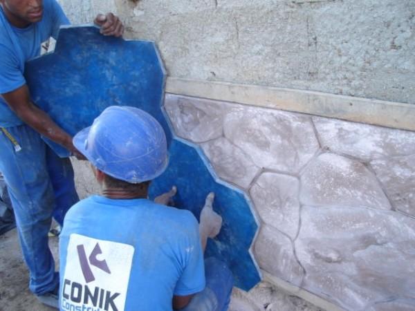 Operários trabalhando da desforma de concreto estampado para paredes