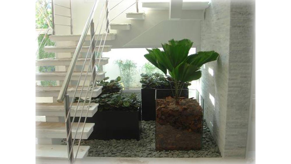 Sob a escada, vasos de folhagens compões esse pequeno jardim de inverno