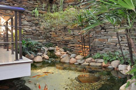 Uma ideia interessante nesse caso foi colocar o lago ornamental sob a varanda, criando uma ideia de suspensão do espaço
