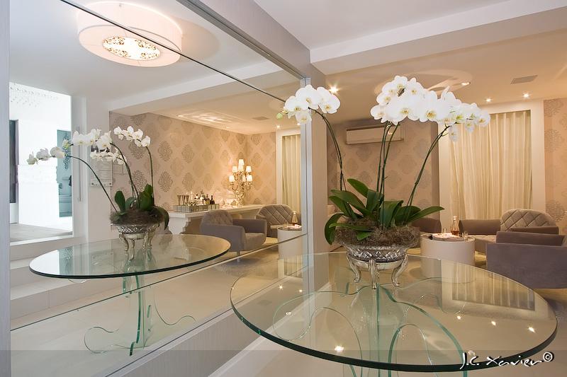 Orquídeas artificias figurando sobre mesas de vidro, dando toque especial na decoração da sala