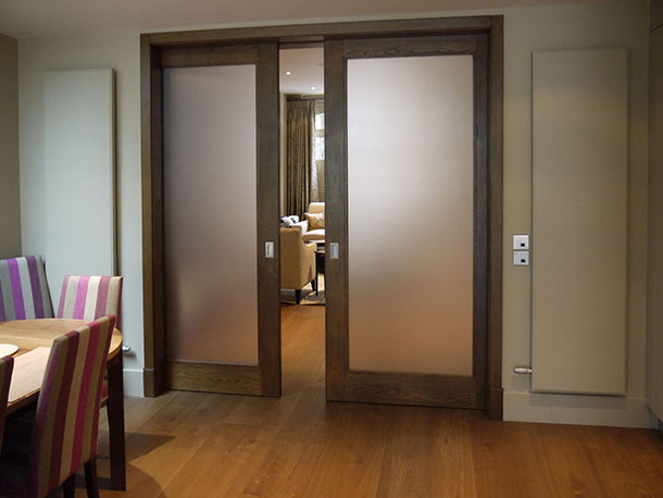 Design mais tradicional em porta com grandes planos de vidro fosco, dupla e de madeira para separar sala de estar e sala de jantar