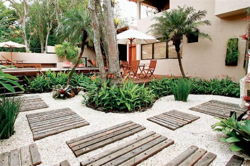Seixos recobrindo o jardim, acompanhado de decks de madeira