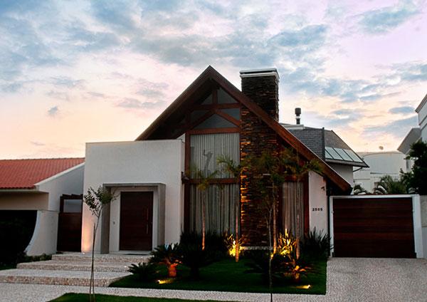 Casa de estilo moderno, com fachada com tons de branco, madeira e vidro