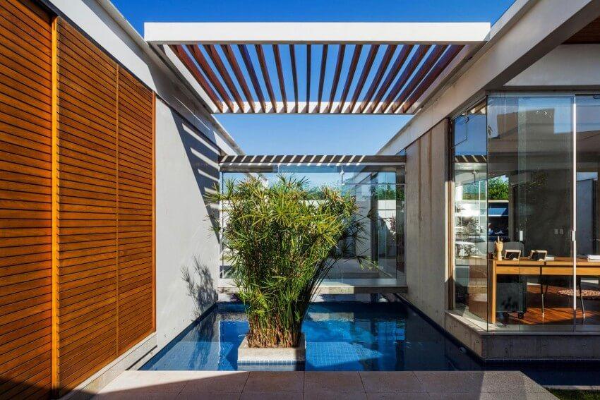Pergolado de madeira sobre espelho d'água em casa moderna