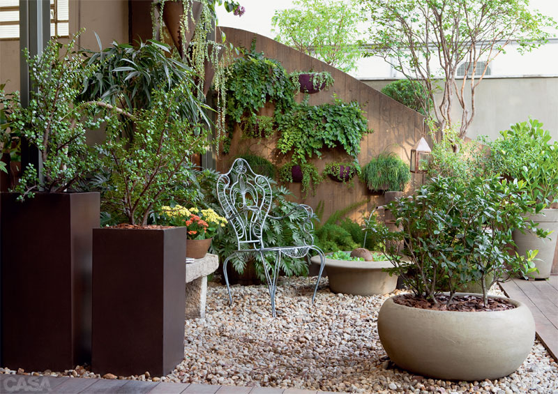 Diversos modelos de vasos para jardim compondo o paisagismo de uma pequena área