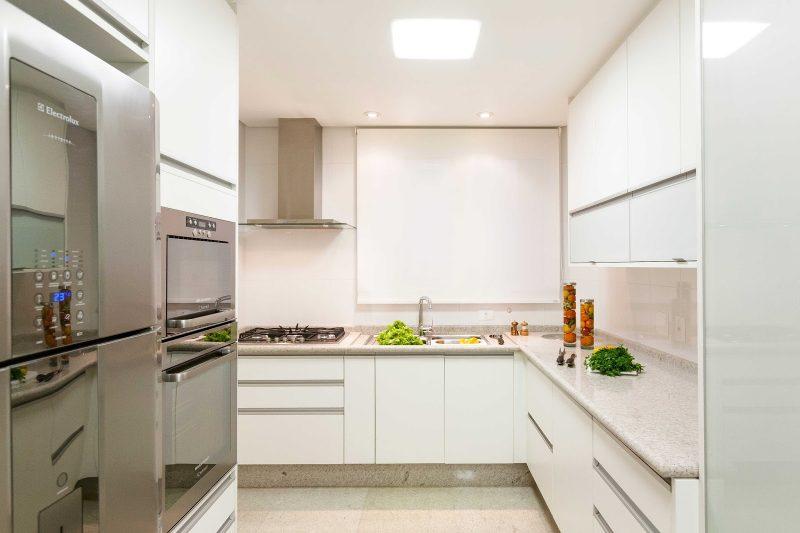 exemplo de bancada em mármore para cozinha com fogão e móveis todos brancos combinando