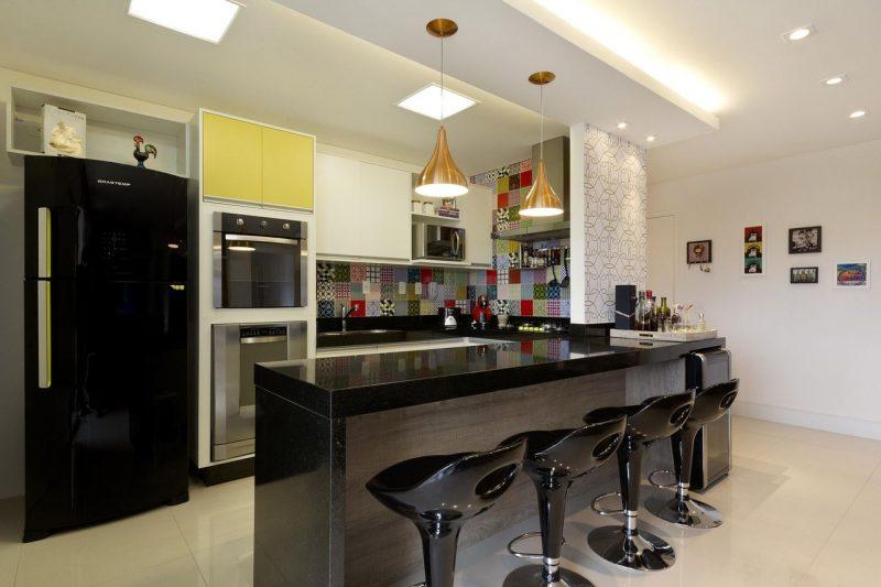 Cozinha americana com iluminação pendente sobre a bancada da cozinha