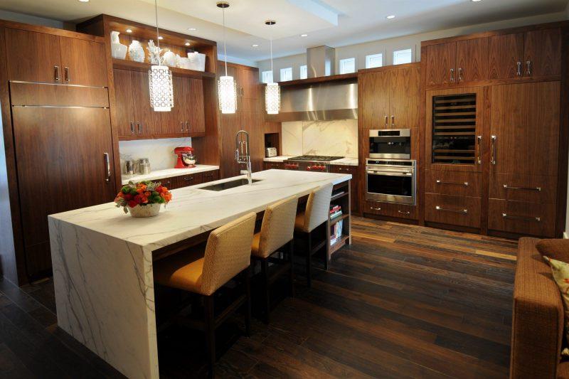 Decoração da cozinha toda em madeira, com o balcão em mármore para diferenciar o nicho do ambiente
