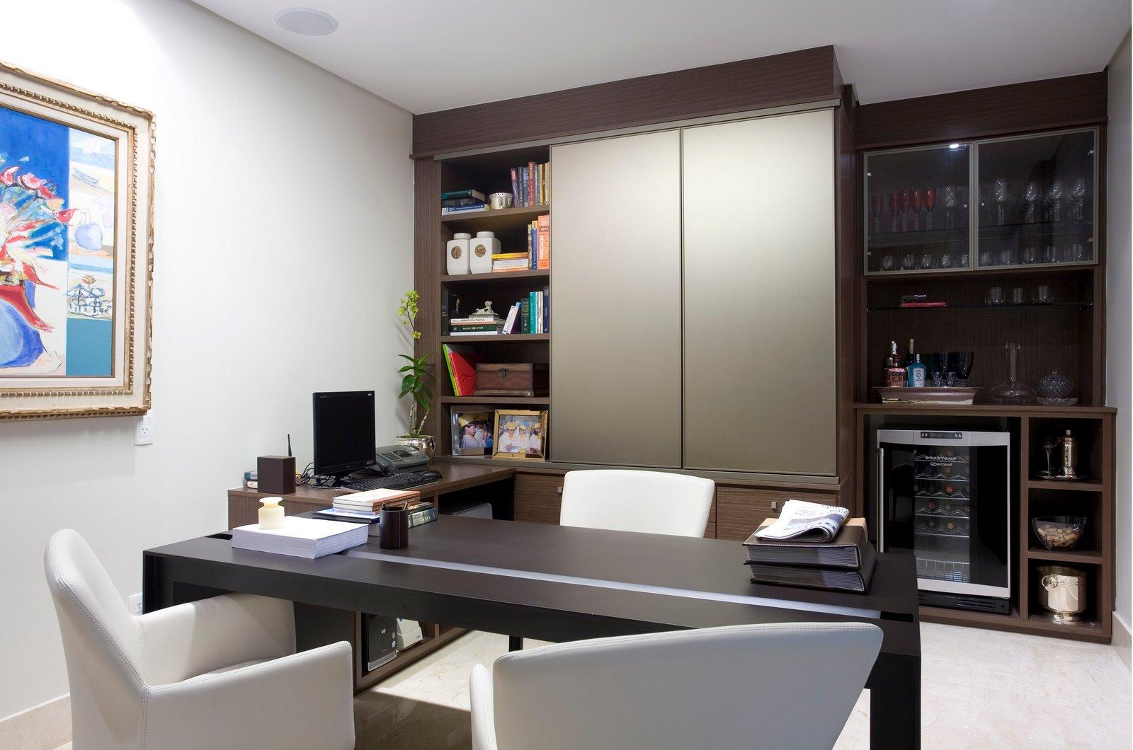 Nesta sala de escritório, as mesas dispostas em L criam uma bancada de trabalho que também serve para atender a clientes, como indicam as cadeiras a frente