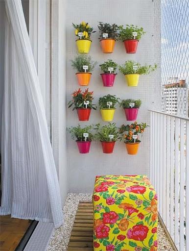Um jardim vertical em uma varanda, com simpáticos vasinhos coloridos.