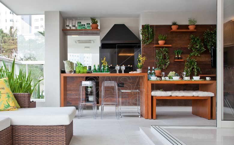 Chique espaço de churrasqueira com bancada e móveis de madeira sob medida