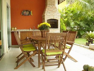 Varanda aberta com churrasqueira e mesa para quatro pessoas
