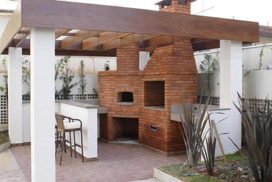 Sob a sombra de um pergolado de madeira externo se localizam bancada e fornos de alvenaria