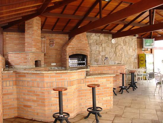 Bancada com tampo de granito e corpo de alvenaria compondo o espaço juntamente com forno e churrasqueira
