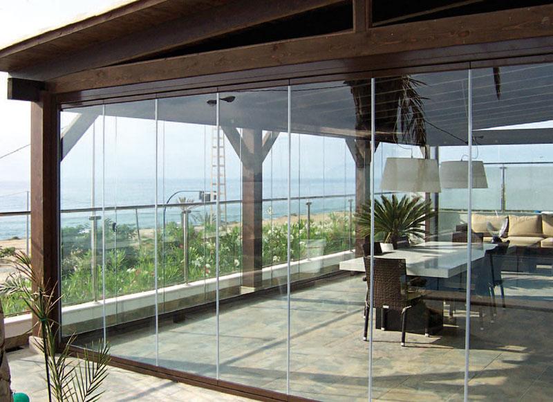 Parede de cortina de vidro em área coberta de varanda, de casa na praia