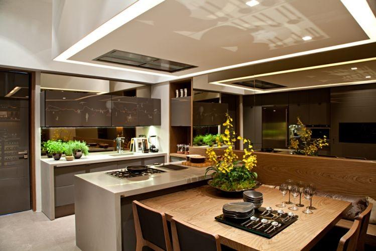 Cozinha prática em U integrada com sala de jantar e espelho para ampliar o ambiente