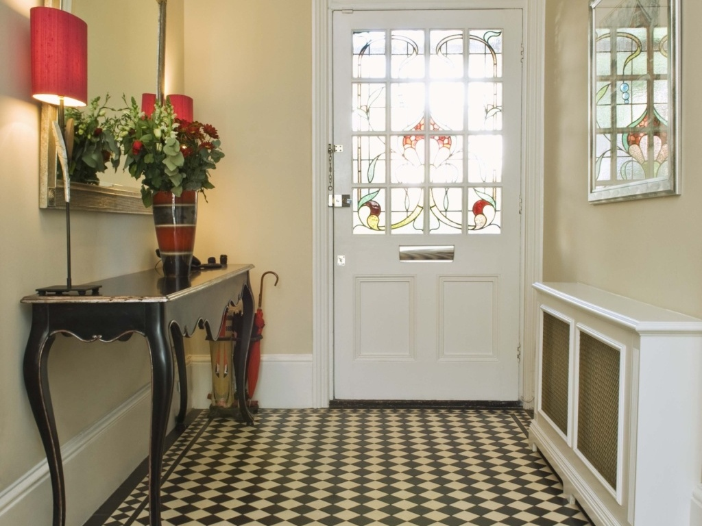 hall na entrada simples decorado com aparadores, flores e espelho, de aspecto bem retrô