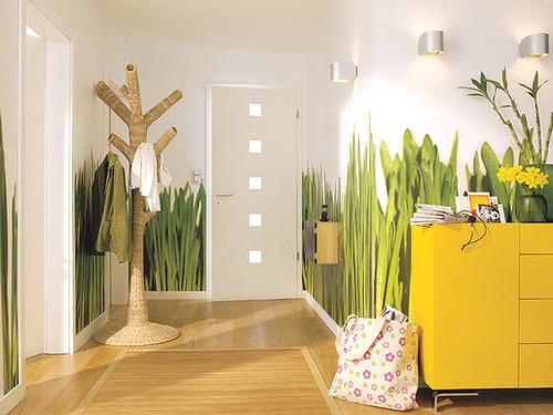 Hall decorado na entrada com papel de parede que simula vegetação
