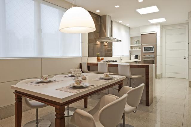 cozinha integrada com sala de jantar. Na cozinha você confere luminárias spots de embutir e na sala um grande pendente sobre a mesa