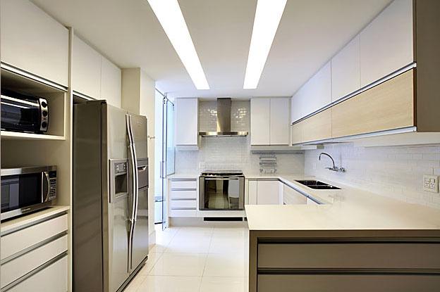 Grandes luminárias lineares de embutir no forro da cozinha