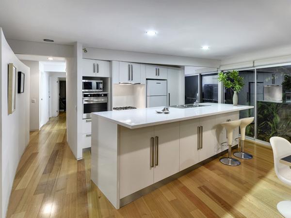 Já esse modelo de espaço gourmet para cozinha trabalha com piso laminado e bancada e móveis brancos