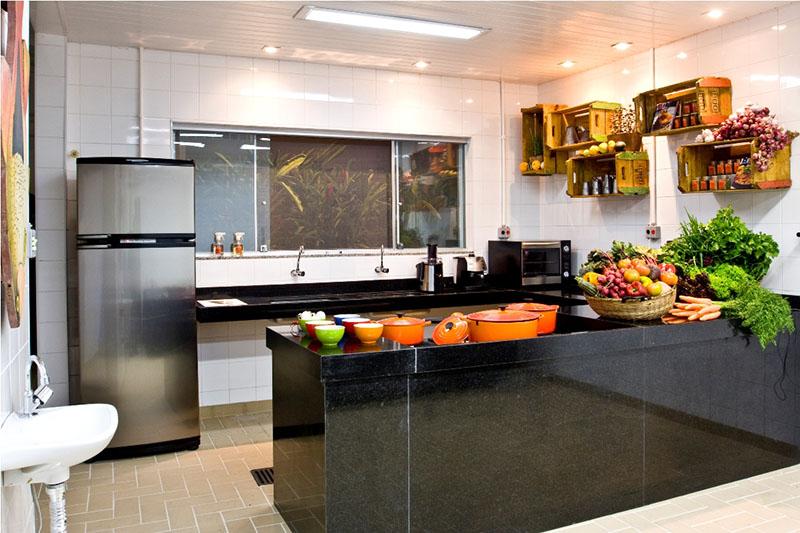 decoração de cozinha com bancada em granito preto e móveis em aço inox