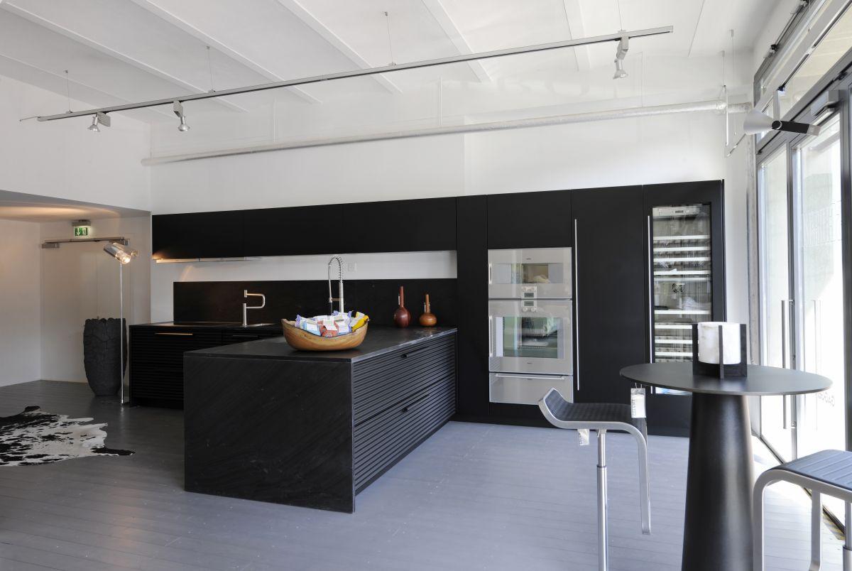 Uma cozinha bem simples preta, com poucos elementos que se sobressaem na decoração