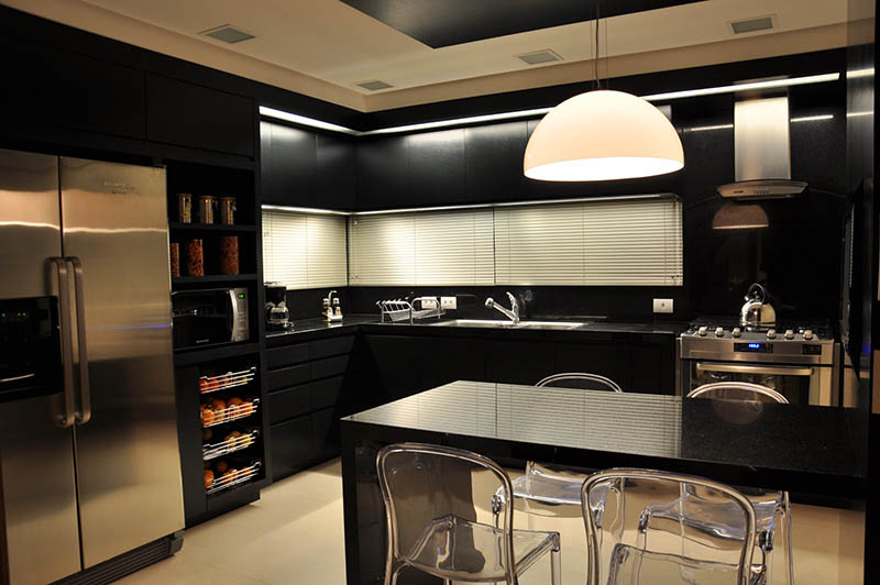 Cozinha super bem iluminada com luminária pendente sobre a mesa