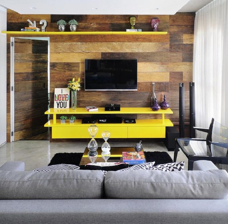 Móveis amarelos fazendo contraste com painel da sala de TV