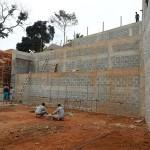 Proteção de grande escarpa do terreno feita por três níveis de muro de blocos de concreto