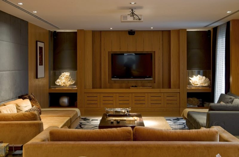 Sala de TV decorada com móveis de madeira escura, dando uma cara mais rústica ao ambiente
