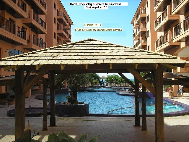 Pequena estrutura para piscina de hotel feita com telhado 4 águas de madeira
